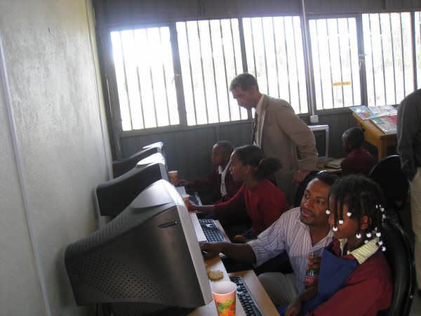 Teachers and volunteers work with kids in the computer lab